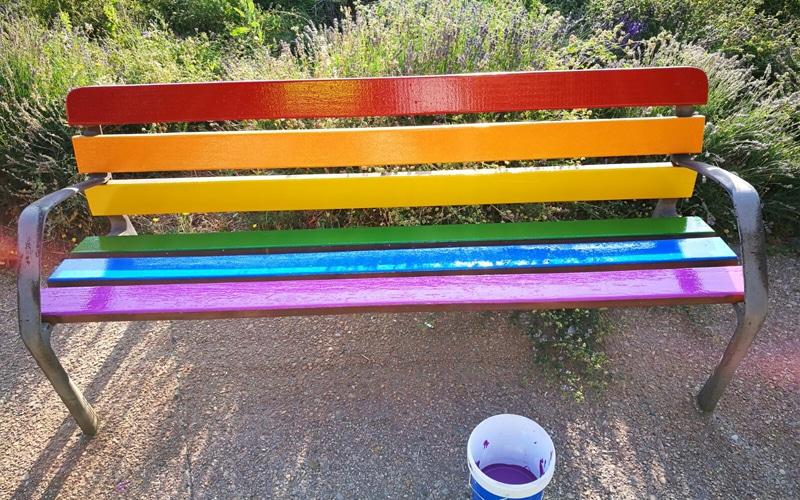 banco del Parque Lineal de Rivas pintado con los colores de la bandera LGTBI