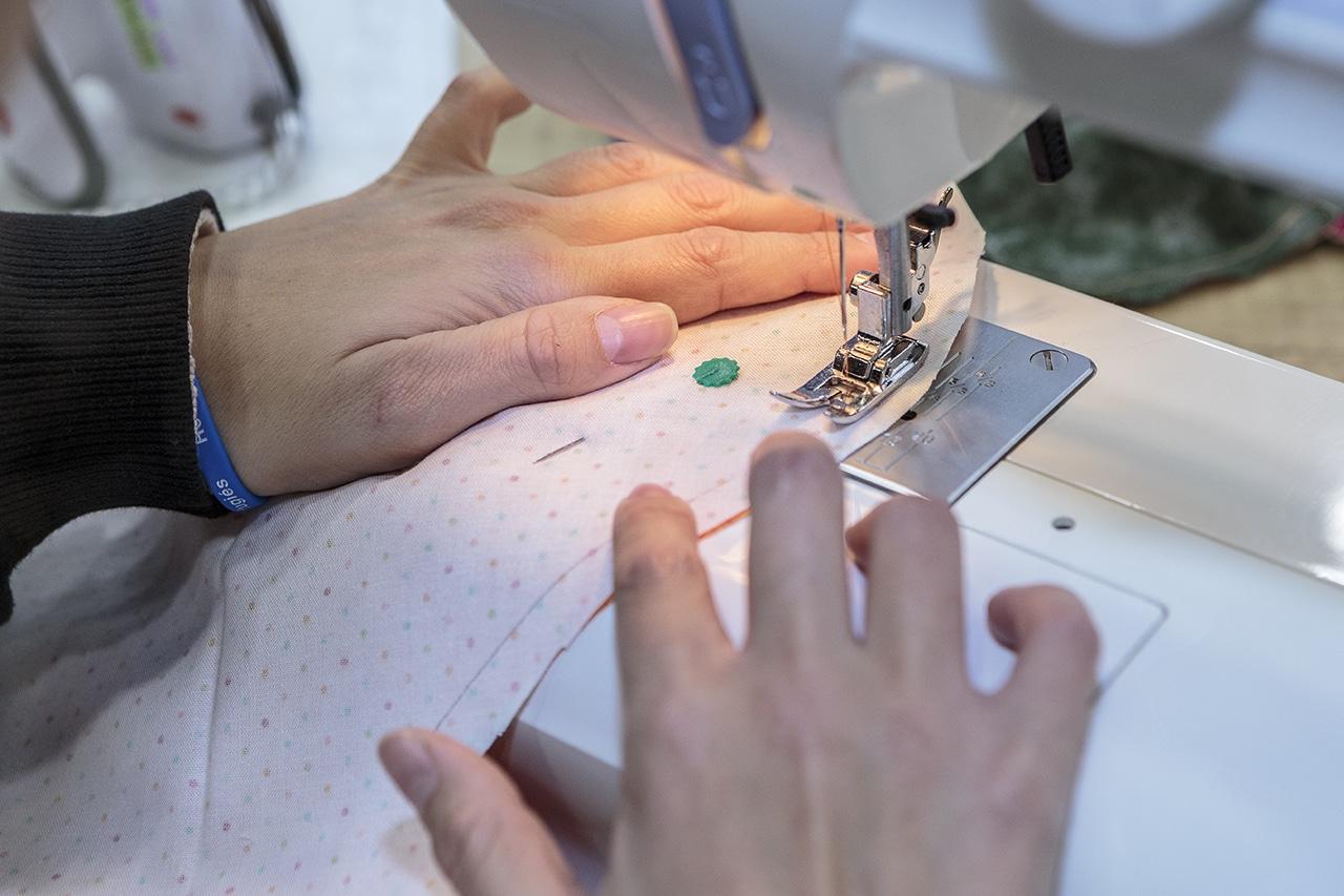 Integrante del taller cosiendo los corazones (Fernando Galán)