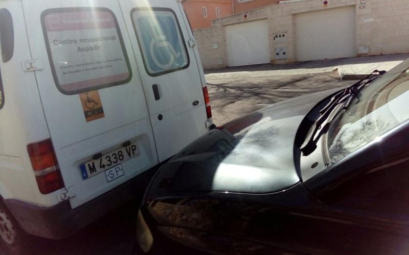 Coche mal aparcado detrás de una furgoneta para personas con discapacidad