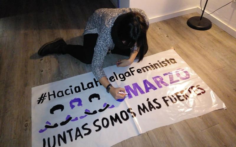 Una mujer de la Asamblea Feminista 8M de Rivas pinta una pancarta para llamar a la huelga de 2018