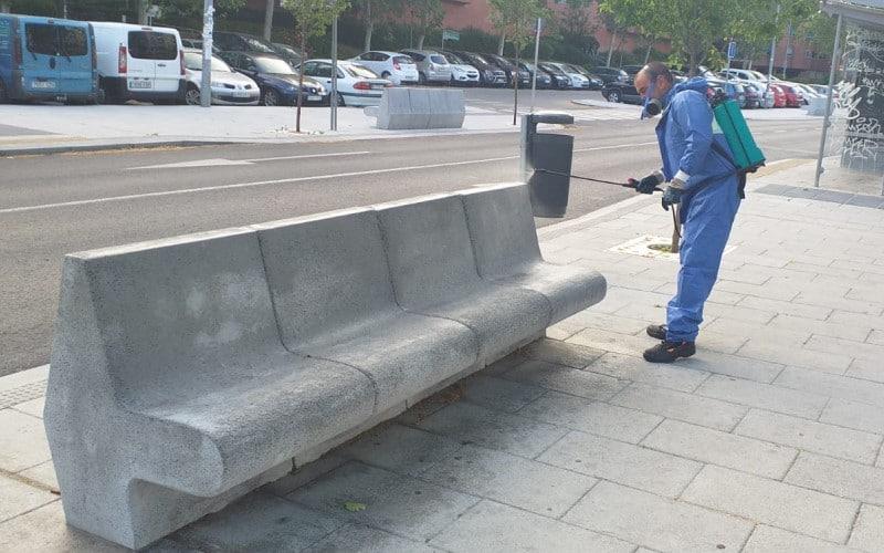 Un operario de Rivamadrid desinfecta un banco en la vía pública
