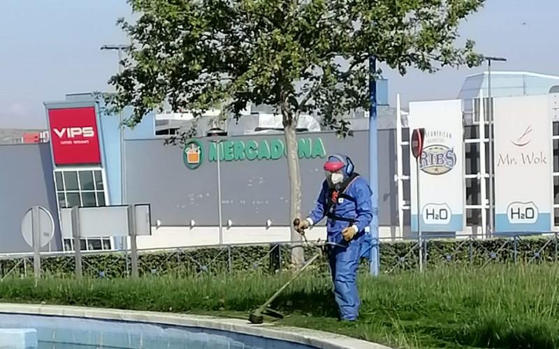 Un trabajador de Rivamadrid realiza tareas de jardinería frente al centro comercial H2O