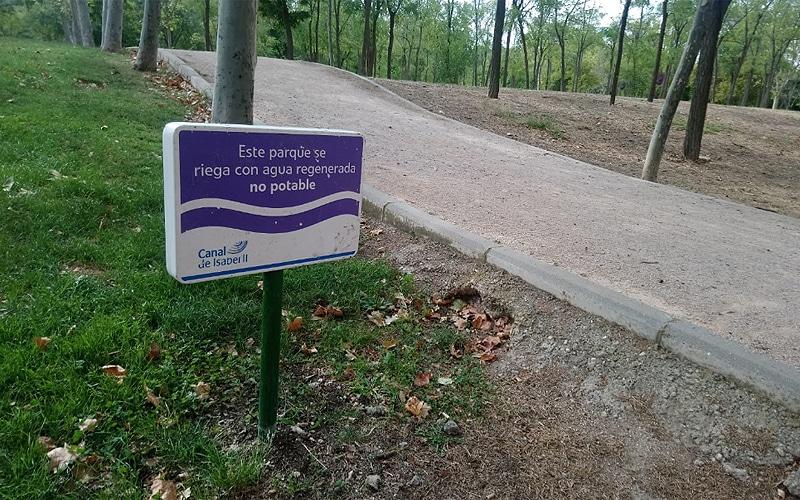 Cartel informativo del riego con agua regenerada instalado en el Parque de Asturias, en Rivas Vaciamadrid