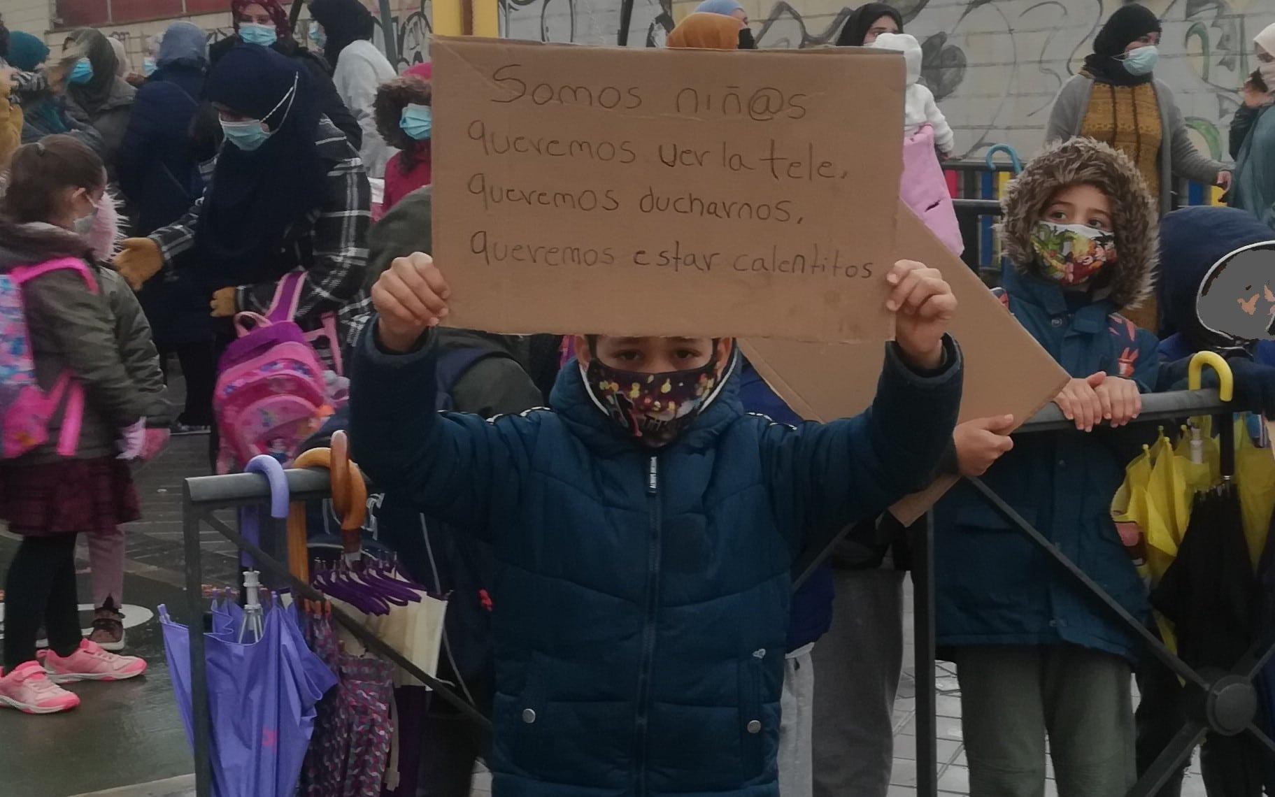 Un niño muestra un cartel en protesta por la falta de luz en la Cañada Real (©Diario de Rivas)