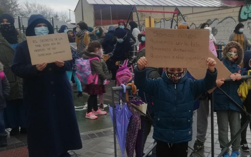 Un niño muestra un cartel en protesta por la falta de luz en la Cañada Real