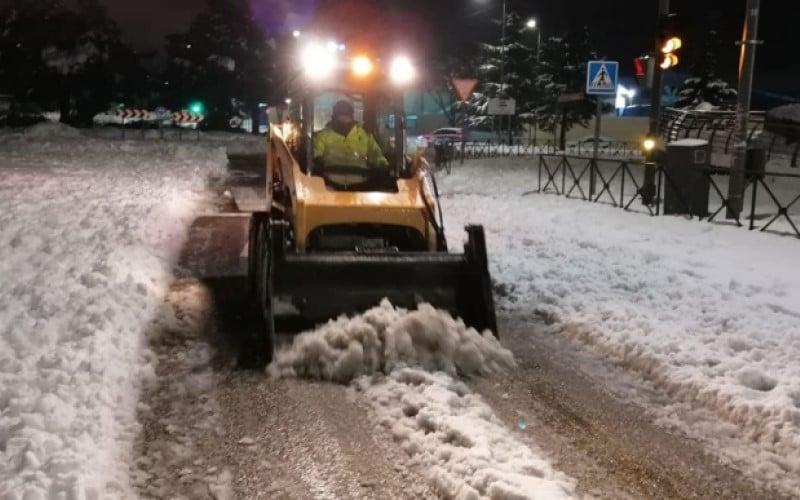 Un vehículo municipal realiza tareas de limpieza de nieve por la noche