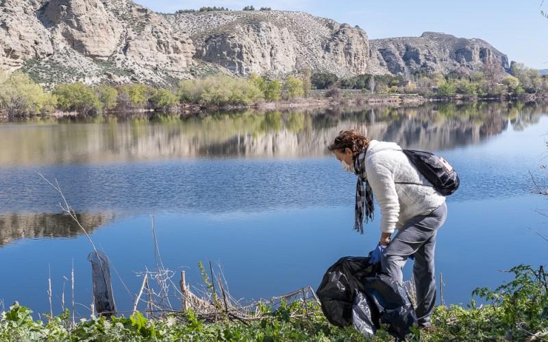 Una voluntaria limpia restos de basura en la Laguna del Campillo