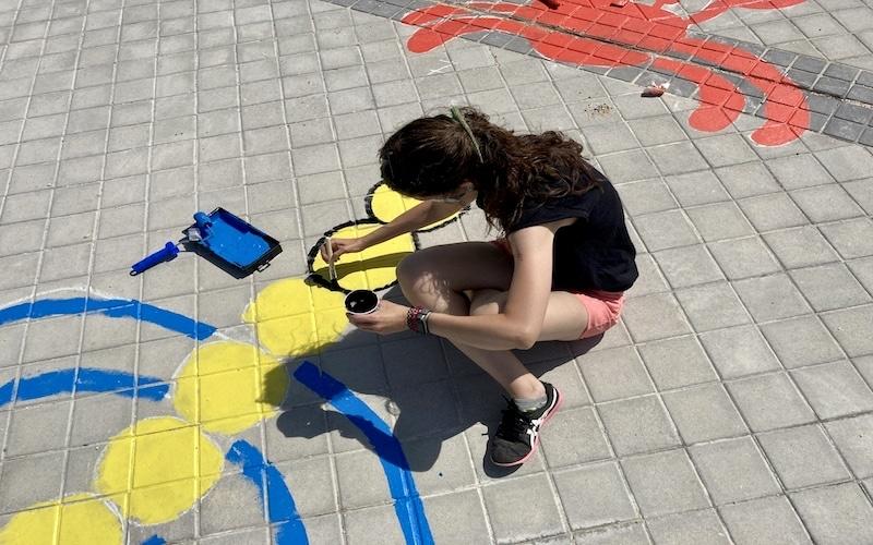 Una de las impulsoras del proyecto, Sonia Goméz, pintando el circuito de rayuelas en el barrio de La Luna
