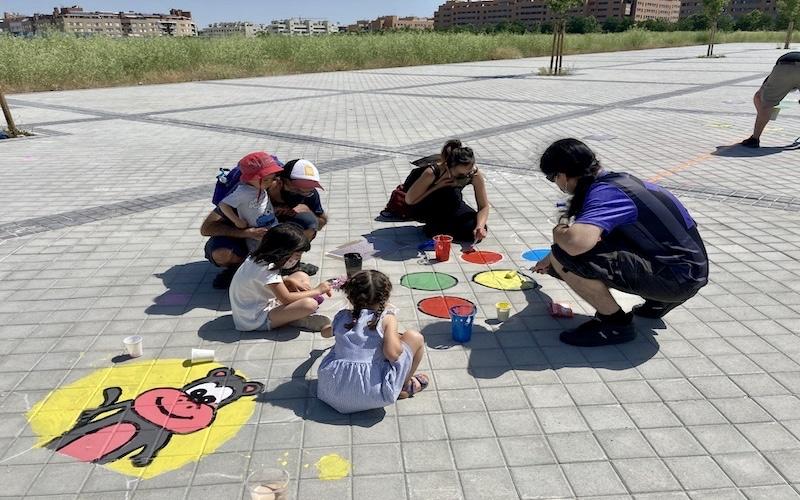 Vecinos y vecinas del barrio La Luna pintando el circuito de rayuelas